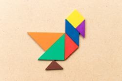 Color tangram puzzle in duck, swan or goose shape on wood background