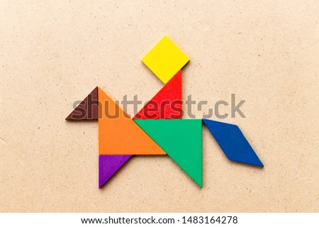 Color tangram puzzle in man ride on the horse shape shape on wood background #1483164278