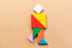 Color tangram puzzle in walking man shape on wood bacground