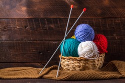 Color thread for knitting, knitted scarf, knitting needles on a dark background. Copy space. Knitting concept