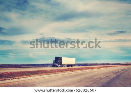 Color toned picture of American highway landscape with semi trailer truck.