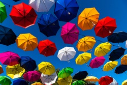 Color umbrellas against a blue sly