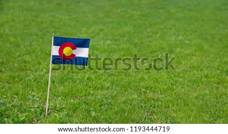 Colorado flag. Photo of Colorado state flag on a green grass lawn background. Close up of Coloradoan flag waving outdoors. #1193444719