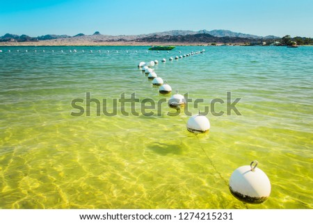 Colorado River at Lake Havasu City landscape background. Line of white buoys and fast boat silhouette in quiet turquoise blue to yellow green clear water. Summer holidays destination in Arizona, USA.