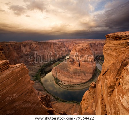 Colorado River snakes around the sandstone cliffs of Horseshoe Bend, with a storm on the horizon