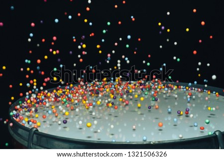 Colored balls bounces off drum in shockwave pattern. Dark background. stock photo