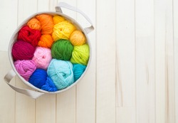 Colored balls of yarn. View from above. Rainbow colors. All colors. Yarn for knitting. Skeins of yarn. Basket with sheep yarn. A set for creativity. Favorite hobby.