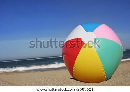 Colored beachball on golden sand beach with blue sky