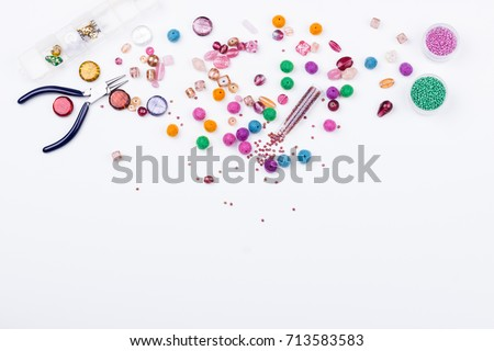 Colored beads. Glass, seed beads and felted beads for jewelry making on white background. Hobby, handmade, fine arts. Selective focus