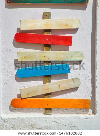 Colored blank wooden signboards pointing to different directions on a white wall.
