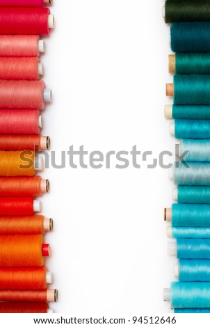 colored bobbins against white background. on the left red and orange bobbins and on the right blue and green