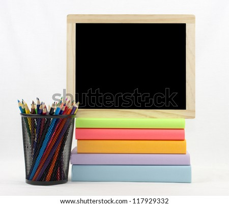 Colored books with colored pencils in holder with chalkboard