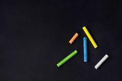 Colored chalk on black blackboard. Negative message space . Yellow, Orange, Blue Chalk. Green Chalk and White Chalk.