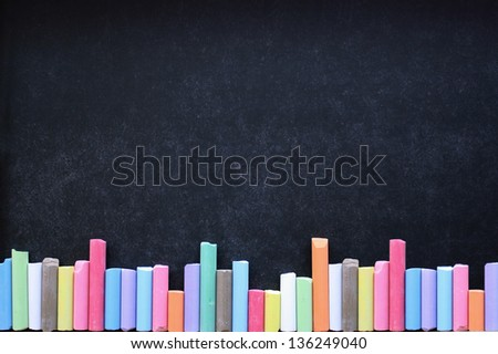 Colored chalks aligned on blackboard
