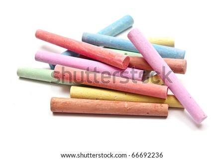 Colored chalks on white background with soft shadows.