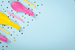 Colored confetti and air balloons composition on blue background, party and celebration decoration. Flat lay, layout and tabletop mockup with copy space.