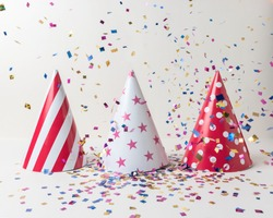 Colored confetti and party hat on white background. Minimal party concept.
