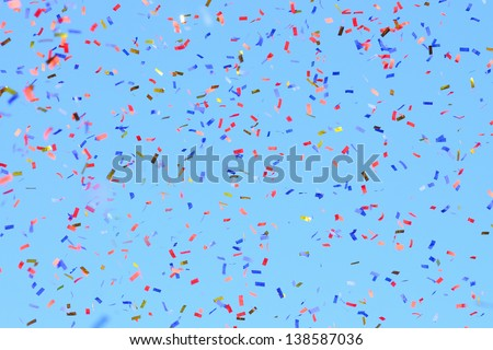 Colored Confetti Flying In The Blue Sky. Are Small Pieces Or Streamers Of Paper, Mylar, Or Metallic Material Which Are Thrown At Parades And Celebrations.