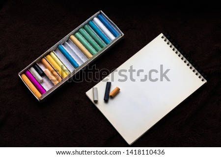 Colored crayons dry pastels and notebook for pastels on a black background #1418110436
