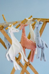 colored cuddly toys giraffes hung up to dry on clothes horse