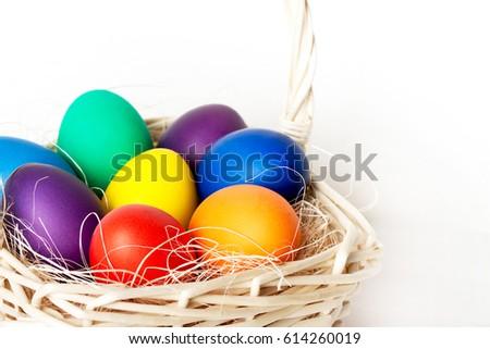 Stock Photo Colored easter eggs in a basket close-up on a light background.