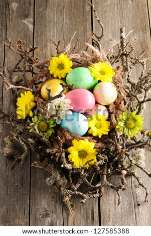 Colored easter eggs in nest on wooden table