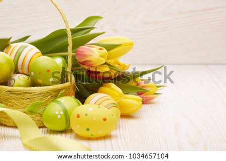 Colored easter eggs in the basket, spring tulips flowers and ribbon on wooden background. Greeting card. #1034657104