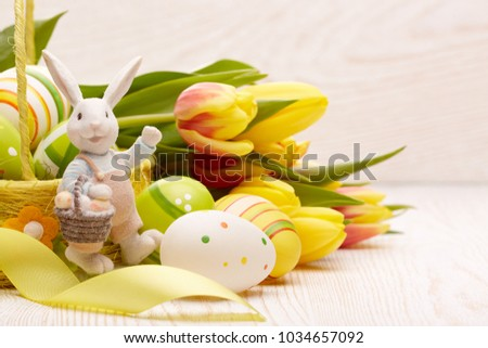 Colored easter eggs in the basket, spring tulips flowers, easter rabbit and ribbon on wooden background. Greeting card. #1034657092
