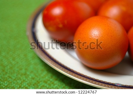 Colored easter eggs on a plate with green background