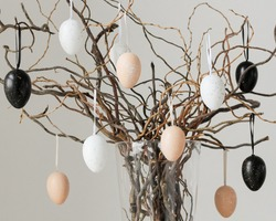 Colored easter eggs on tree branches in vase