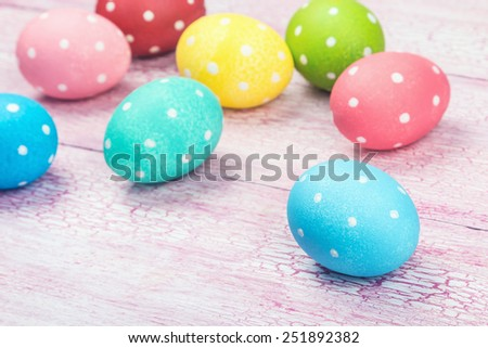 colored Easter eggs on wooden background. Focus on a blue egg #251892382