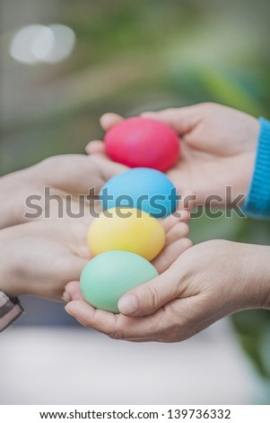 colored eggs in the hands of mother and child