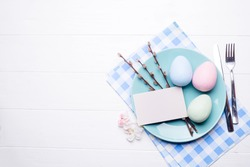 colored eggs on blue plate with flowers on white wooden background, flat lay