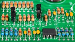Colored electronic components. Resistors, transistors, capacitors and integrated circuit on PCB. Standard color code. Green copper board detail. Dismantled computer hardware. Electrotechnics, e-waste.