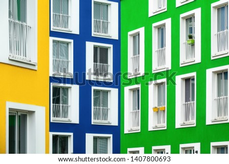 Colored facades of residential buildings in the colors yellow, blue and green.  The white window frames stand out sharply and flower boxes are hanging on the balcony railings #1407800693