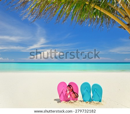 Colored flip flops and sunglasses at the sunny beach -- Tropical beach vacation and travel concept