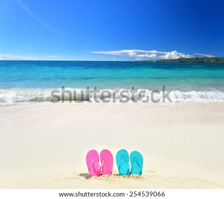 Colored flip flops on the sunny beach -- Tropical beach vacation and travel concept