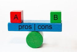 colored fragments in fragile balance with the words pros | cons. On top of the seesaw are a red block with A and a green Block with B