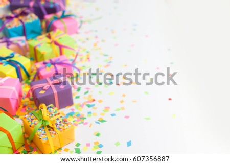 Colored gift boxes with colorful ribbons and confetti. White background. Gifts for Christmas or a birthday. #607356887