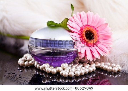 colored glass bottles exclusive perfume on the background of feathers and pearls and flowers with water drops