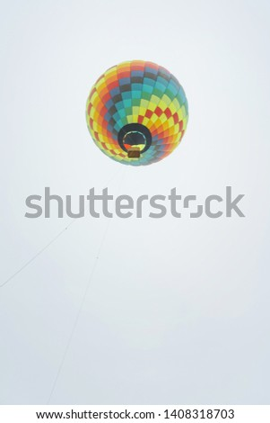 Colored hot air balloon on light sky background bottom-up view. Festival hot air balloons. Multicolored balloon in the sky close-up