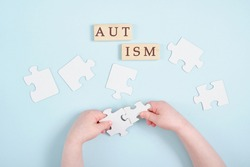 colored kids hands hold puzzles on blue background, autism symbol, autism diagnosis concept, inscription autism on wooden dominoes