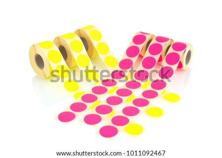 Colored label rolls isolated on white background with shadow reflection. Color reels of labels for printers. Labels for direct thermal or thermal transfer printing. Yellow and pink labels background. #1011092467