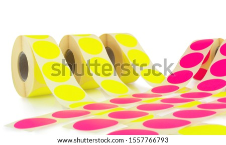 Colored label rolls isolated on white background with shadow reflection. Color reels of labels for printers. Labels for direct thermal or thermal transfer printing. Close-up shot. Label wallpaper.