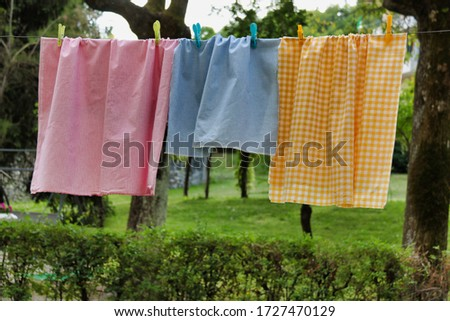 Photo of  colored laundry hanging on the clothesline outdoors