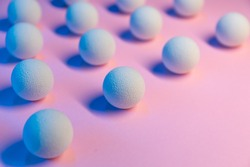 Colored light shines on white balls on a pink background