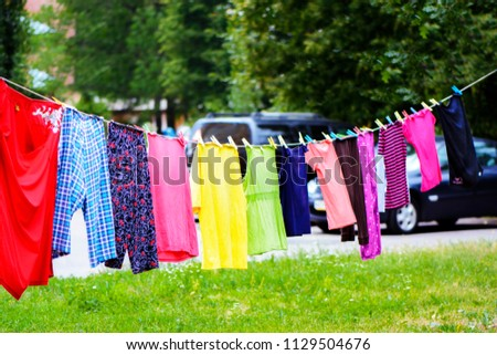 colored linen is dried on a rope #1129504676