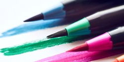 Colored marker pens with brush stroke lines on white paper background Macro Selective focus