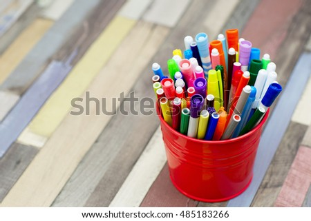 Colored markers in a metal bucket. Different children's felt  pens for painting on wooden background.