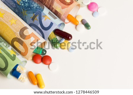 Colored medical pills from rolled up euro banknotes, money from pharmaceutical industry concept  #1278446509